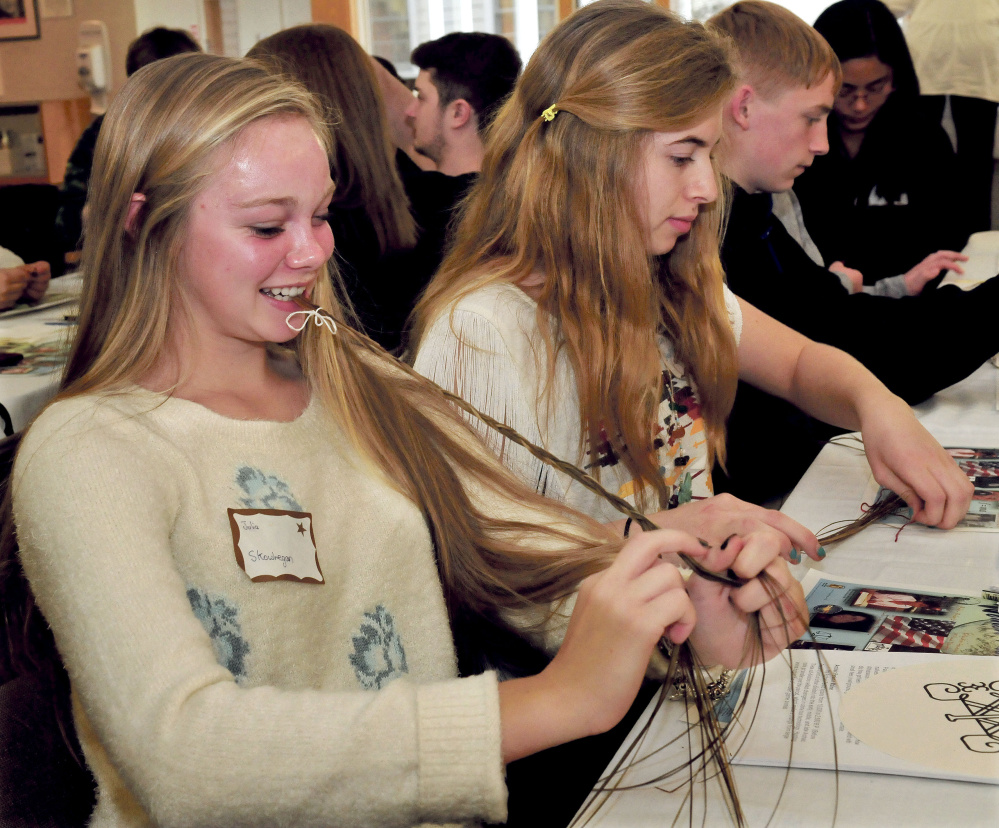 Skowhegan Area High School students Julia Steeves, left, and Anessa McGann and students from Carrabec and Upper Kennebec Valley high schools try their hands at making prayer braids taught by Pam Outdusis Cunningham of the Penobscot tribe during a forum on Maine's Wabanaki tribes and cultures Thursday at the Margaret Chase in Skowhegan