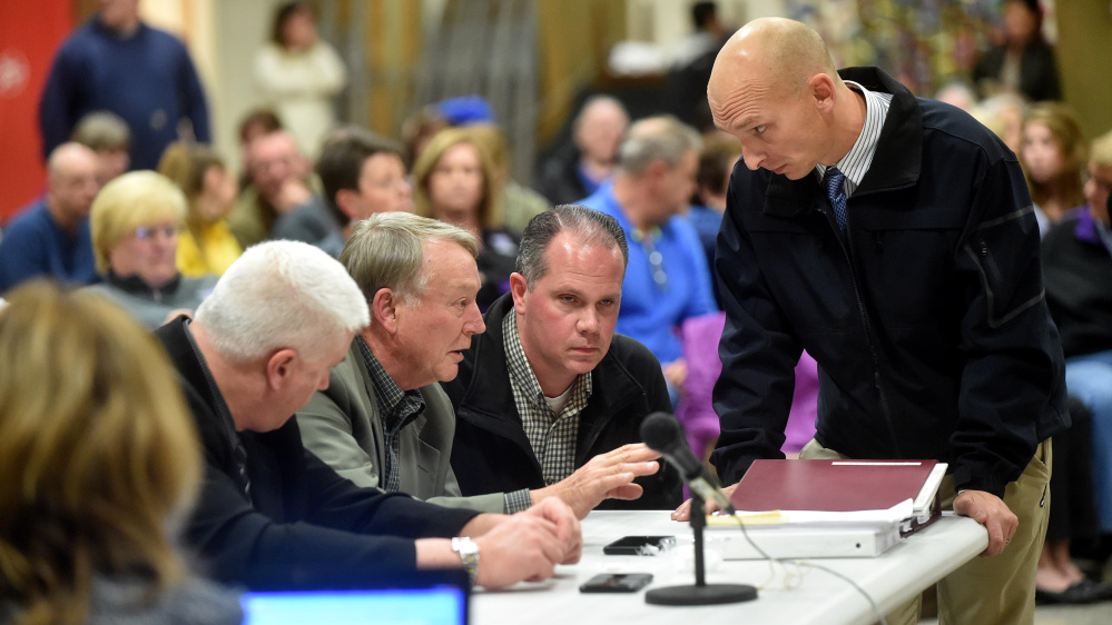 Eric Haley, left center, superintendent of schools, confers with Waterville police detectives Dave Caron, right center, and Bill Bonney, far right, during the public portion Wednesday night of the Waterville Senior High School Principal Don Reiter's dismissal hearing.