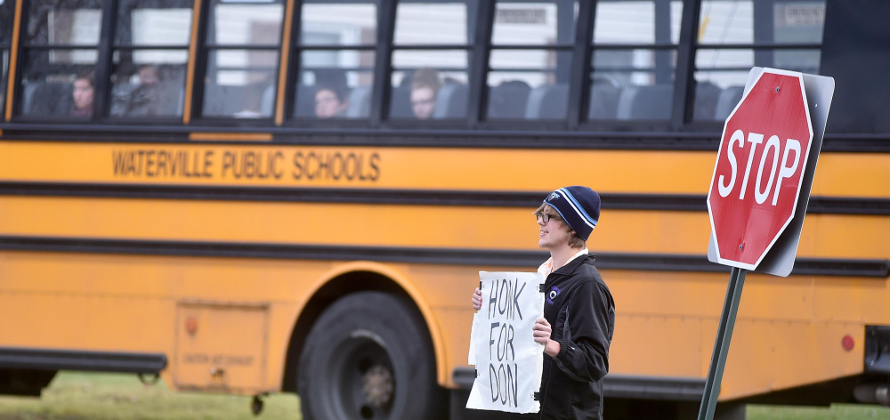 A Waterville Senior High School student stands at the exit to the high school with a sign in support of Waterville Senior High School principal, Don Reiter, at a rally after school Friday. Reiter, accused of propositioning a student, has been on administrative leave since Sept. 1.