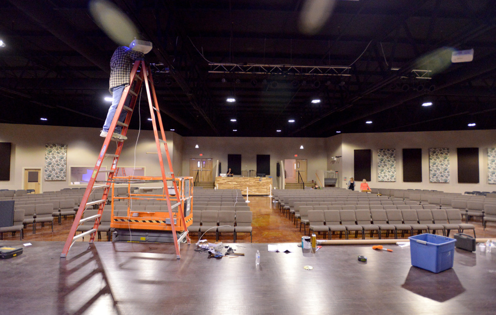 Bill Wade, assistant pastor at Centerpoint Community Church, finishes wiring the stage in the worship auditorium at CenterPoint Church in Waterville. The former Sparetime Recreation bowling alley was renovated for the church, which is hosting a concert Saturday night and its first service in the building  Sunday.