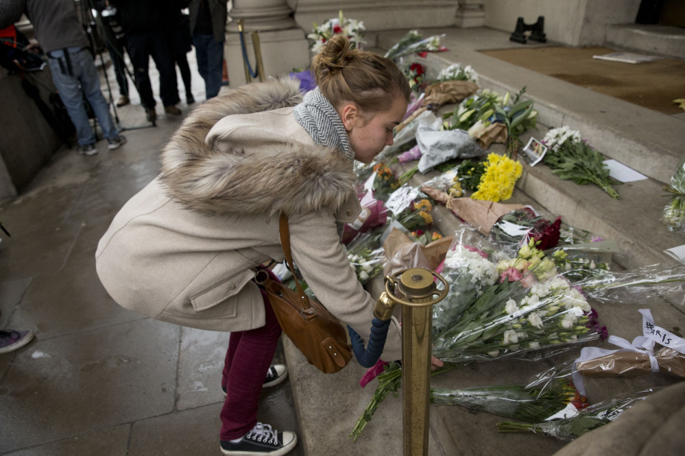 A woman lays flowers for the victims of the deadly attacks in Paris, outside the French embassy in London, on Saturday. French President Francois Hollande said more than 120 people died Friday night in shootings at Paris cafes, suicide bombings near France's national stadium and a hostage-taking slaughter inside a concert hall.