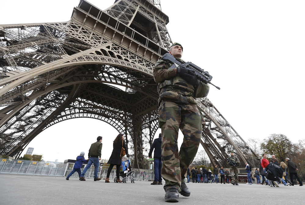 The French military patrols Saturday near the Eiffel Tower, a day after terrorist attacks at seven sites in Paris killed 129 people and injured 352 more. All seven attackers died: six in suicide blasts while the seventh was shot by police.