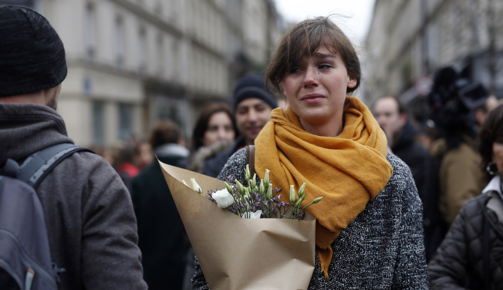 A woman carries flowers in Paris on Saturday. A California college who was spending a semester abroad was the sole American among the dead.