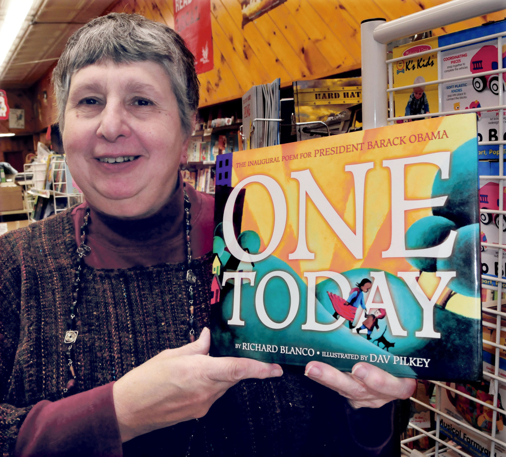 "Waterville bookstore owner Ellen Richmond holds a copy of ""One Today"" by Bethel poet Richard Blanco. Richmond, who owns the Children's Book Cellar, is hosting a reading and signing for Blanco that will be held in the Waterville Opera House Deb. 15."