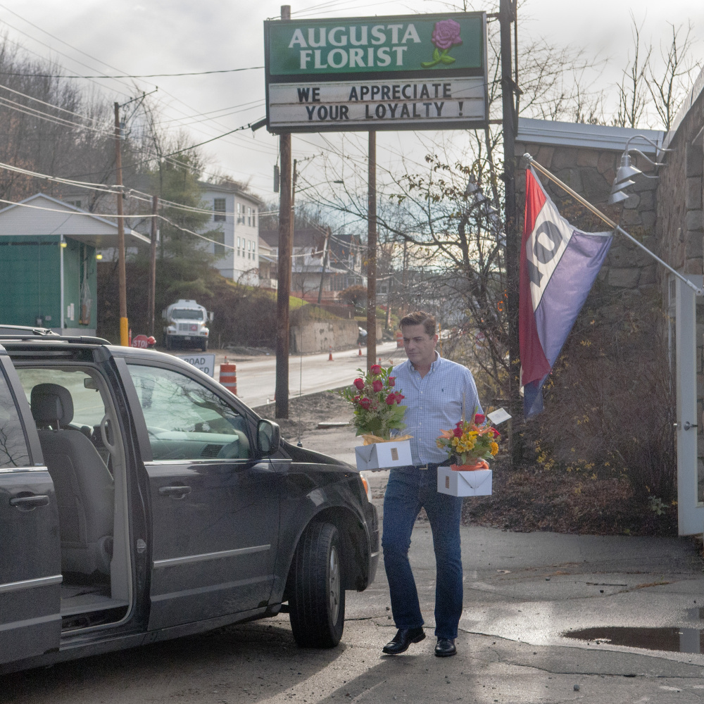 Augusta florist Scott O'Brien carries flowers out to his van on Mount Vernon Avenue in Augusta to make deliveries on Friday. Construction is winding down for the season.