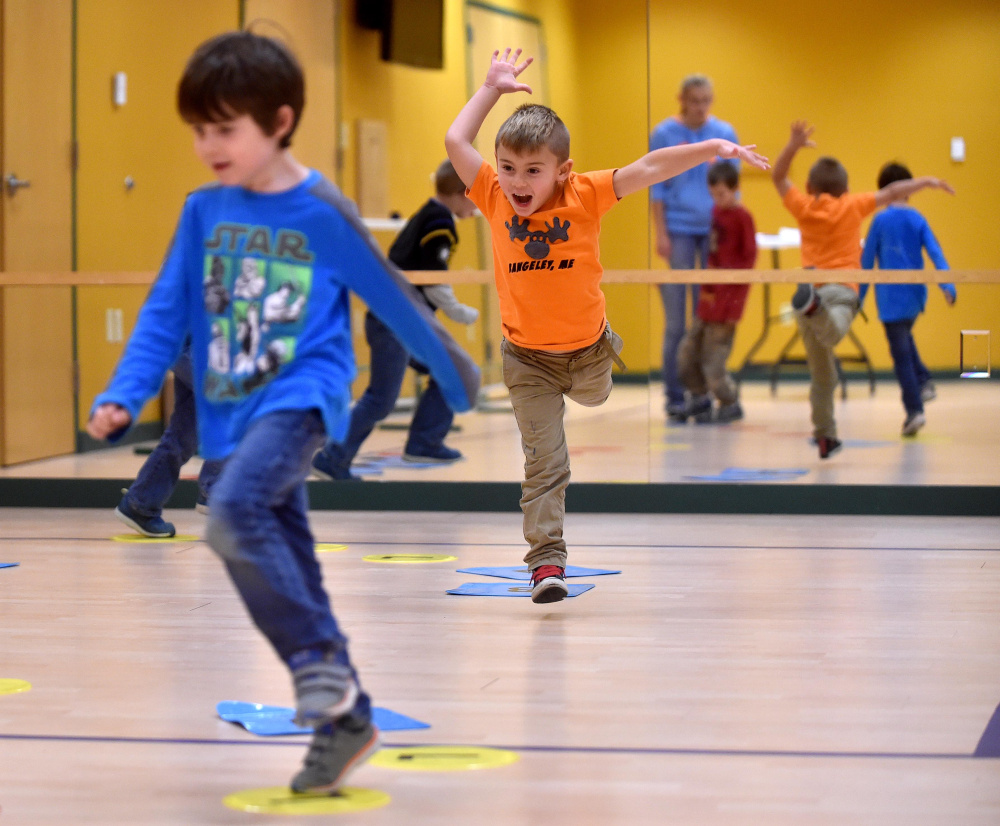 Keagan Talbert, left, and Ryan Dugan, back, play chocolate river in which they have to leap from circle to circle to get across the invisible river during the Children in Action after school program that involves physical and nutritional activities at the Rangeley Health and Fitness Center in Rangeley Thursday.