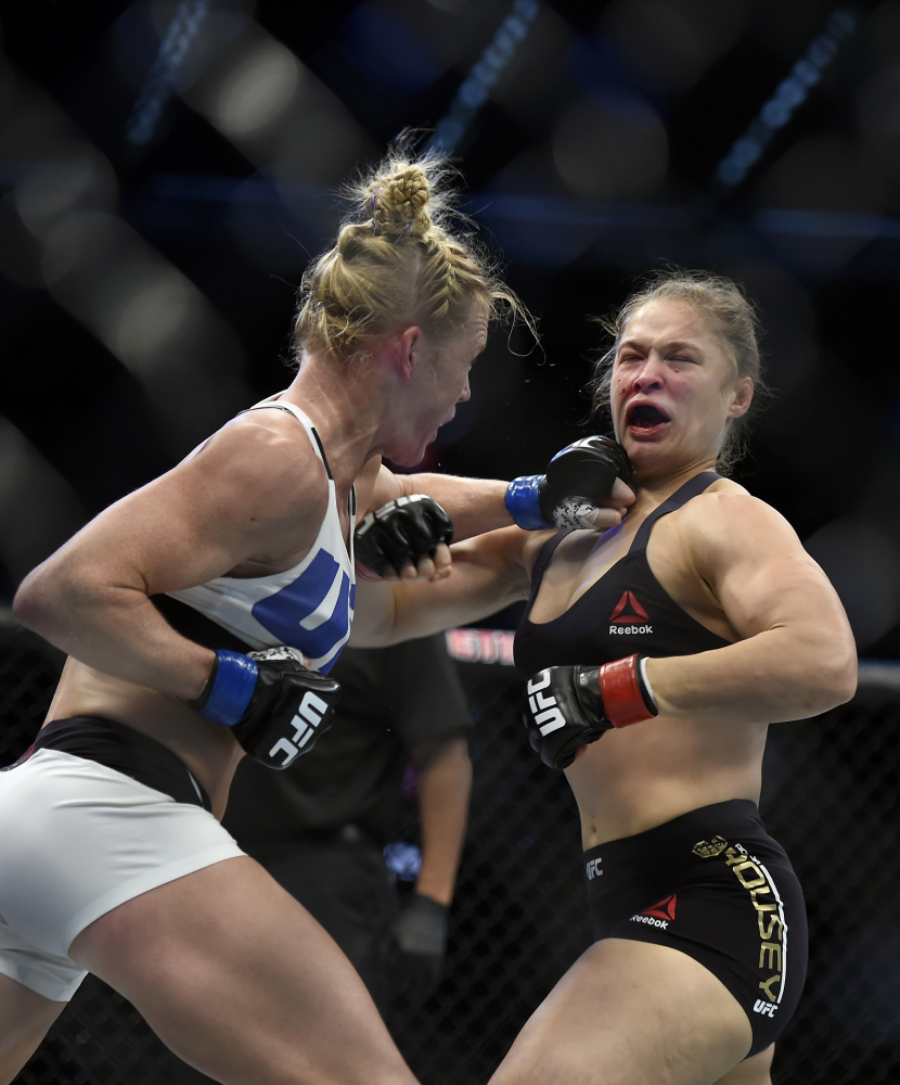 Holly Holm, left, punches Ronda Rousey during their UFC 193 bantamweight title fight Sunday in Melbourne, Australia. Holm pulled off a stunning upset victory over Rousey, knocking out the women's bantamweight champion in the second round with a powerful kick to the head.