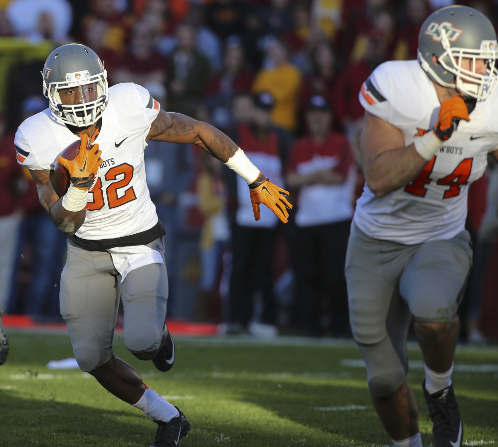 Oklahoma State running back Chris Carson runs for a touchdown during the first half against Iowa State on Saturday in Ames, Iowa. The Cowboys moved up to No. 4 after winning 35-31.