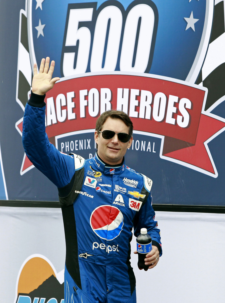 Series points leader Jeff Gordon waves to the crowd during driver introductions before the NASCAR Sprint Cup Series race Sunday at Phoenix International Raceway in Avondale, Ariz. The race was delayed by rain.