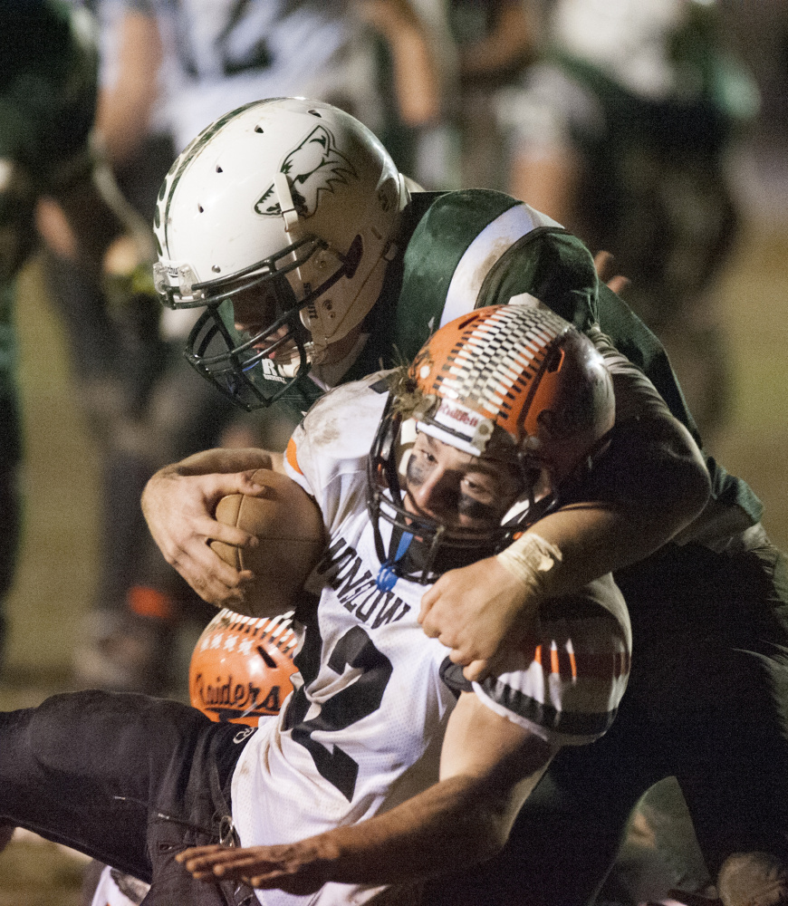 Winslow running back Nate St. Amand is tackled by Old Town's Andre Miller during the Class C North championship game last Friday night in Old Town.