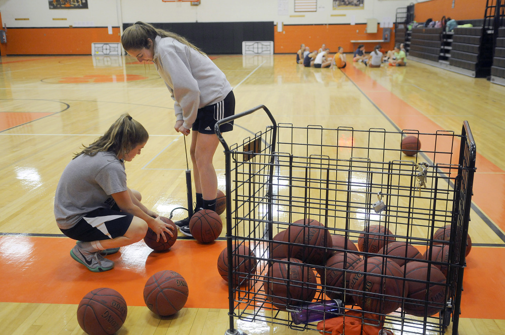 Gardiner Area High Schoo's Mary Toman, right, and Lauren Chadwick pump up some basketballs at the start of tryouts Monday in Gardiner.