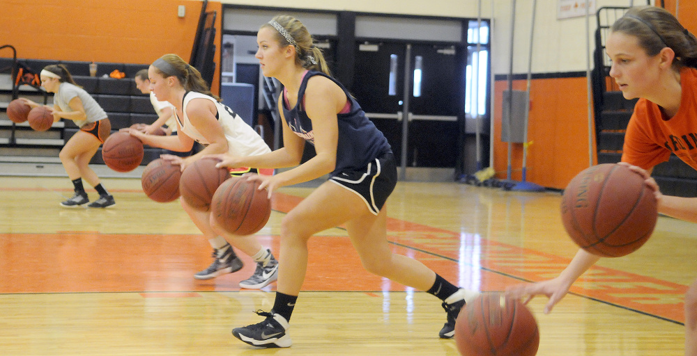 The Gardiner Area High School girls basketball team does dribbling drills at the first day of tryouts Monday in Gardiner.