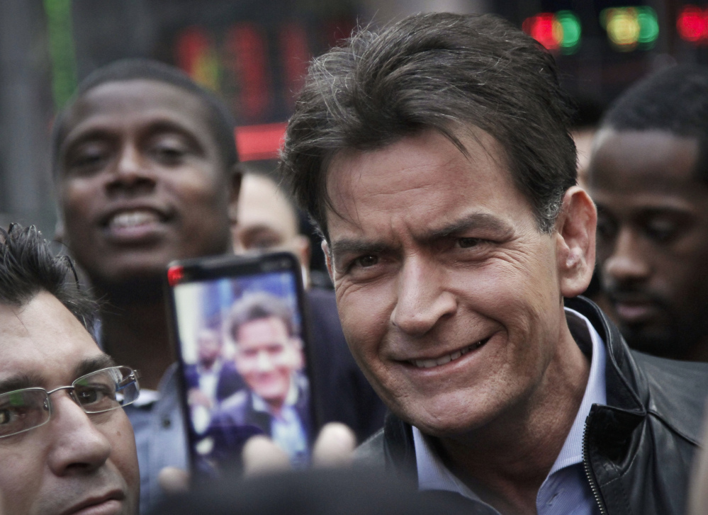 In this Monday, Jan. 14, 2013, file photo, actor Charlie Sheen is mobbed for autographs and photos as he makes his way through Times Square in New York.