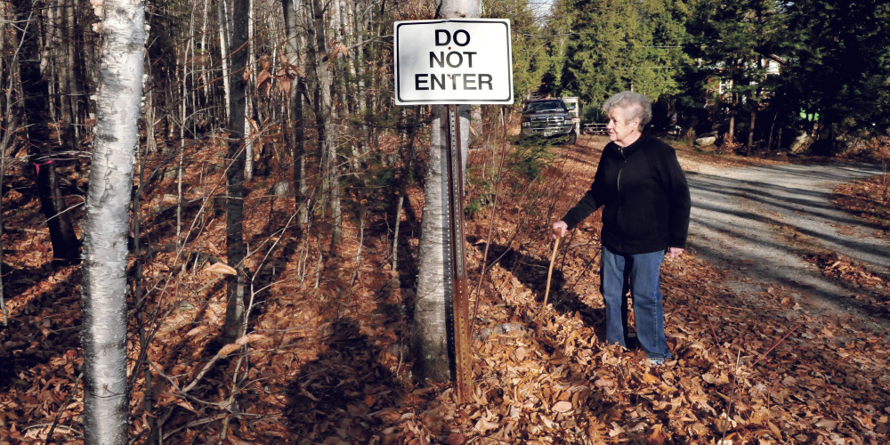 Doris Jorgensen stands beside the sign near her home on Long Pond and property where a proposed summer camp may be built off Jorgensen Estate Road in Rome on Monday.