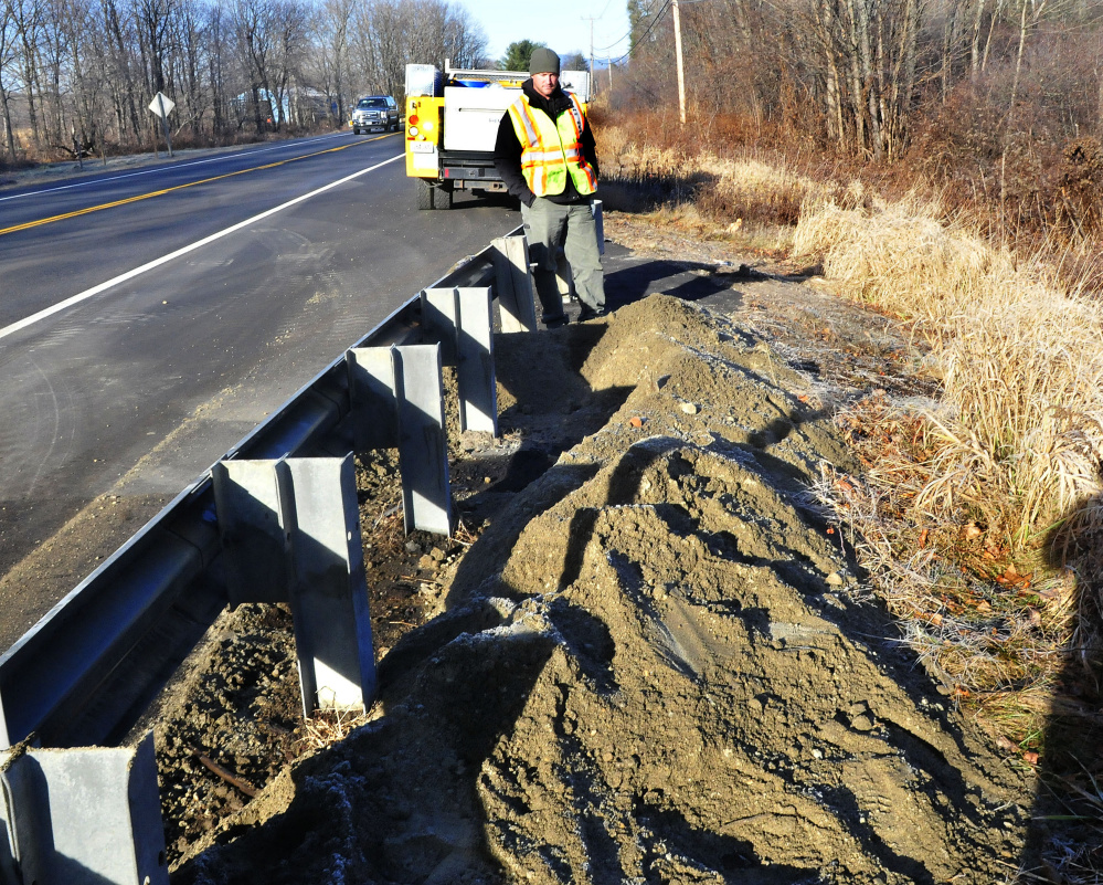 Jeremy Greenman, an oil and hazardous materials responder with the Department of Environmental Protection, surveys the scene along U.S. Route 2 in Farmington on Wednesday where an oil tank truck overturned, spilling some fuel, after a minivan crashed into it Tuesday night.