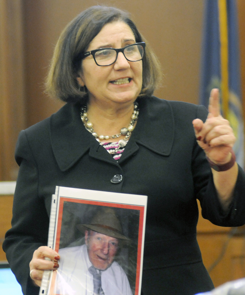 Assistant Attorney General Leane Zainea holds a photo of murder victim Aurele Fecteau Wednesday during closing arguments of the trial of Roland J. Cummings in Augusta.