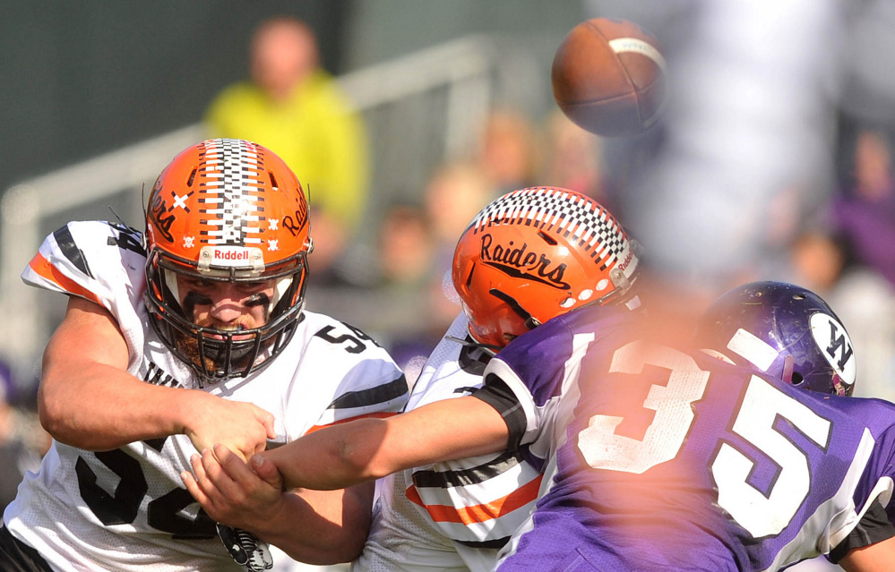 Winslow linebackers Alec Clark (54) and Patrick Hopkins, center, break up a pass intended for Waterville's Devon Begin during a Big Ten Conference game earlier this season at Drummond Field in Waterville.