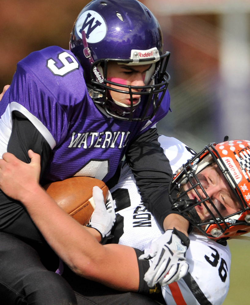 Waterville's Demetrius Ramirez (9) is tackled by Winslow's Kenny Rickard during a Big Ten Conference game at Drummond Field in Waterville.