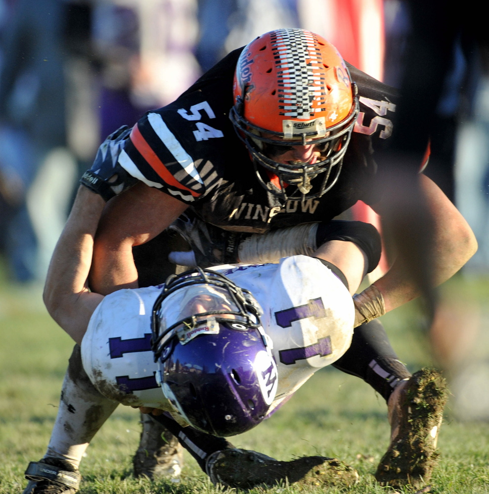 Winslow High School's Alec Clark, top, hits Waterville's Daniel Jolin during the 2014 conference title game.