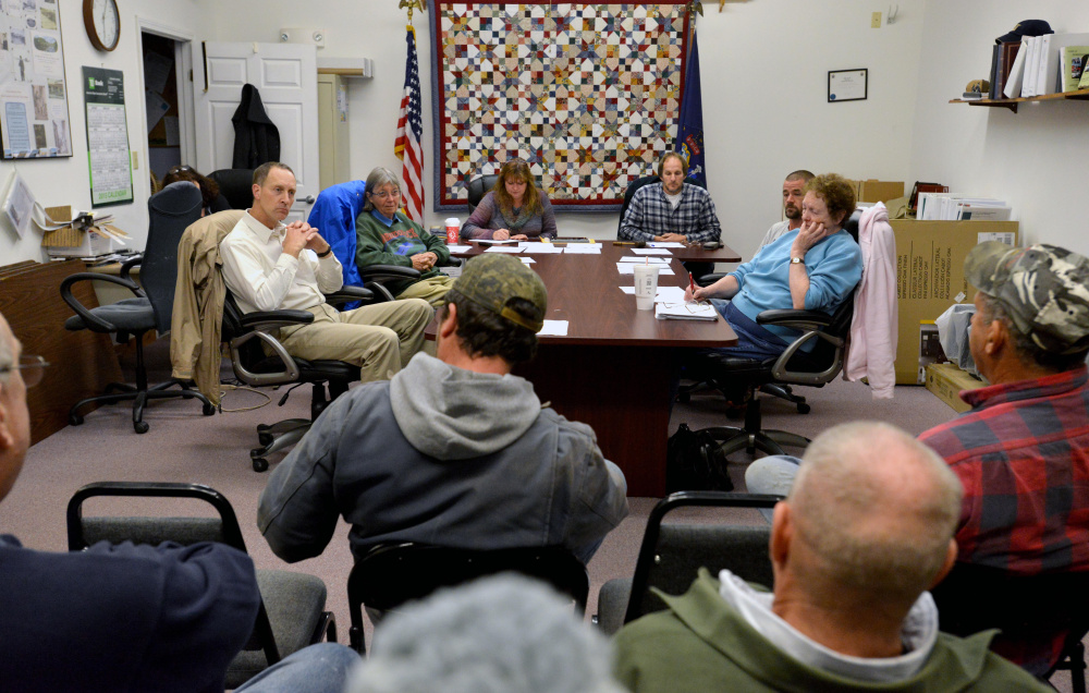Norridgewock selectmen sit at a table as residents fill the room for an open session meeting at the town office in Norridgewock on Wednesday