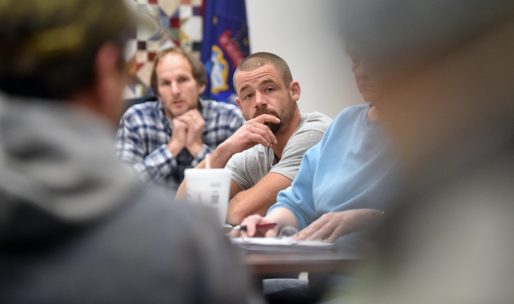 Ron Frederick, chairman of the board of selectmen, left background, and Matt Everett, vice-chairman, center, listen as town residents voice concerns during an open session at the town office in Norridgewock on Wednesday regarding what they would like to see in the next town manager.