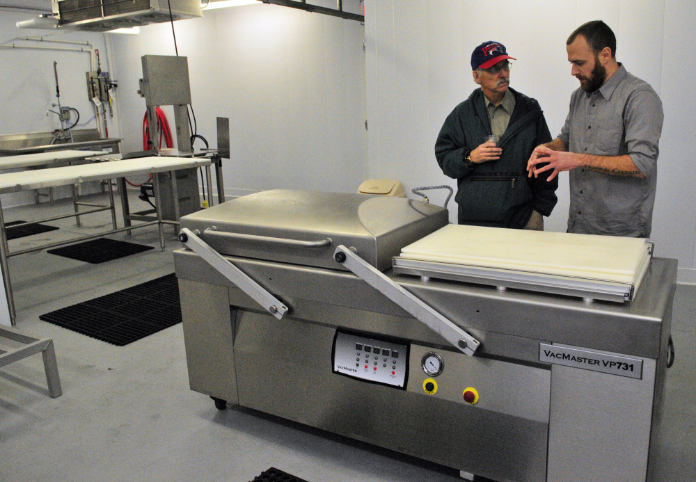 City councilor Phil Hart, left, talks about a cryovac packaging machine with Eben Harrington, the hazard analysis and critical control points manager, during a tour of Central Maine Meats processing facility in Gardiner on Thursday.