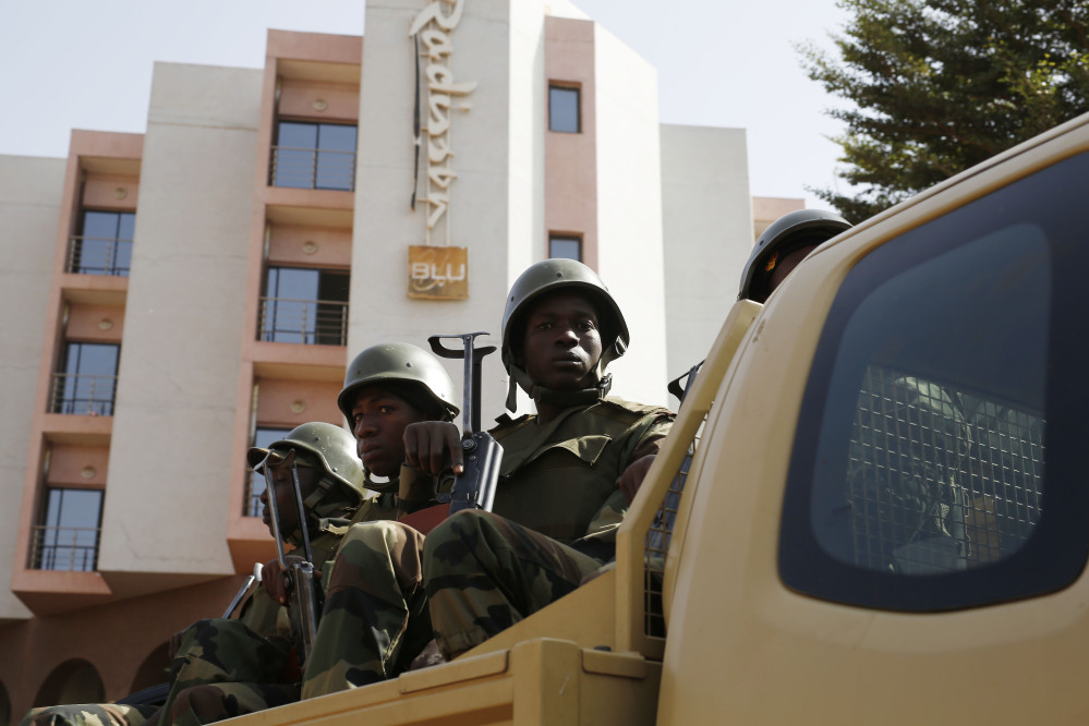 """Soldiers from the presidential guard patrol outside the Radisson Blu hotel in Bamako, Mali, on Saturday in anticipation of the President's visit.  Malian security forces were hunting """"more than three"""" suspects after a brazen assault on a luxury hotel in the capital that killed 20 people plus two assailants, an army commander said."""