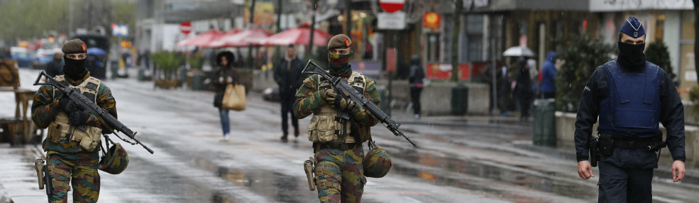 Belgian soldiers and a police officer patrol in central Brussels, Saturday, after security was tightened in Belgium following the fatal attacks in Paris.