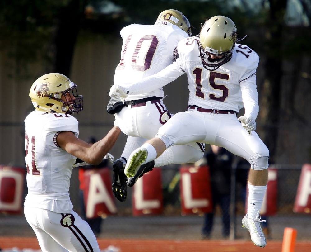 Thornton Academy players Greg Ruff, left, Benjamin Lambert, 10, and Cameron Cadorette celebrate in the second quarter after Lambert intercepted a pass in Saturday's Class A state football championship at Fitzpatrick Stadium.