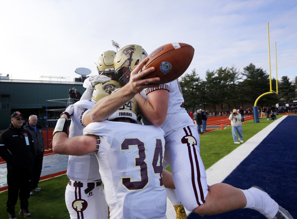 Thornton Academy quarterback Austin McCrum has the football and the joy of his teammates after scoring the fourth-quarter touchdown that put the game away.