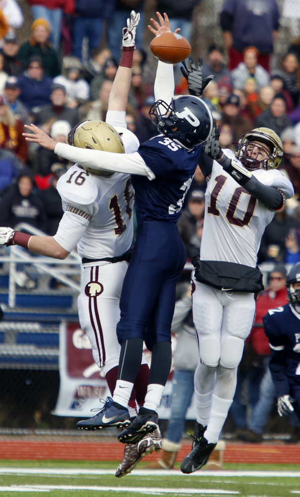 Michael Laverriere, left, and Ben Lambert of Thornton Academy combine to knock away a first-half pass intended for Dylan Bolduc of Portland. Thornton led 14-0 at halftime before Portland rallied to tie.