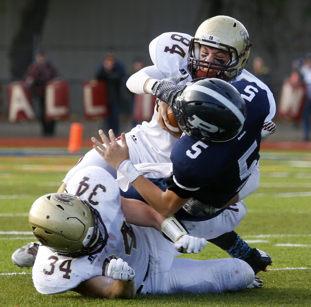 Portland quarterback Issiah Bachelder is unable to avoid a Thornton Academy defensive surge that includes Evan Russell, top, and Owen Elliott.