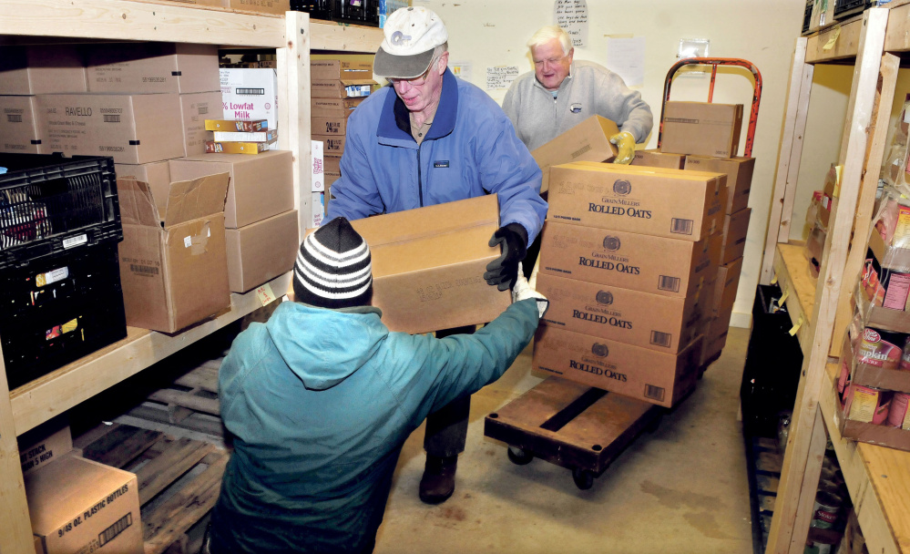 These volunteers load food onto shelves at the Care and Share Food Closet in Farmington on Wednesday. From left are Carl Hutchinson, Dave Scribner and board member Dana Bullen.