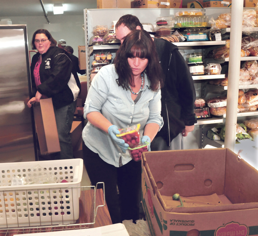 Care and Share Food Closet volunteers prepare to fill a cooler with vegetables at the Farmington group's building on Wednesday. From left are Heather Hodsdon, Lee Spaulding and Ann Flanders.