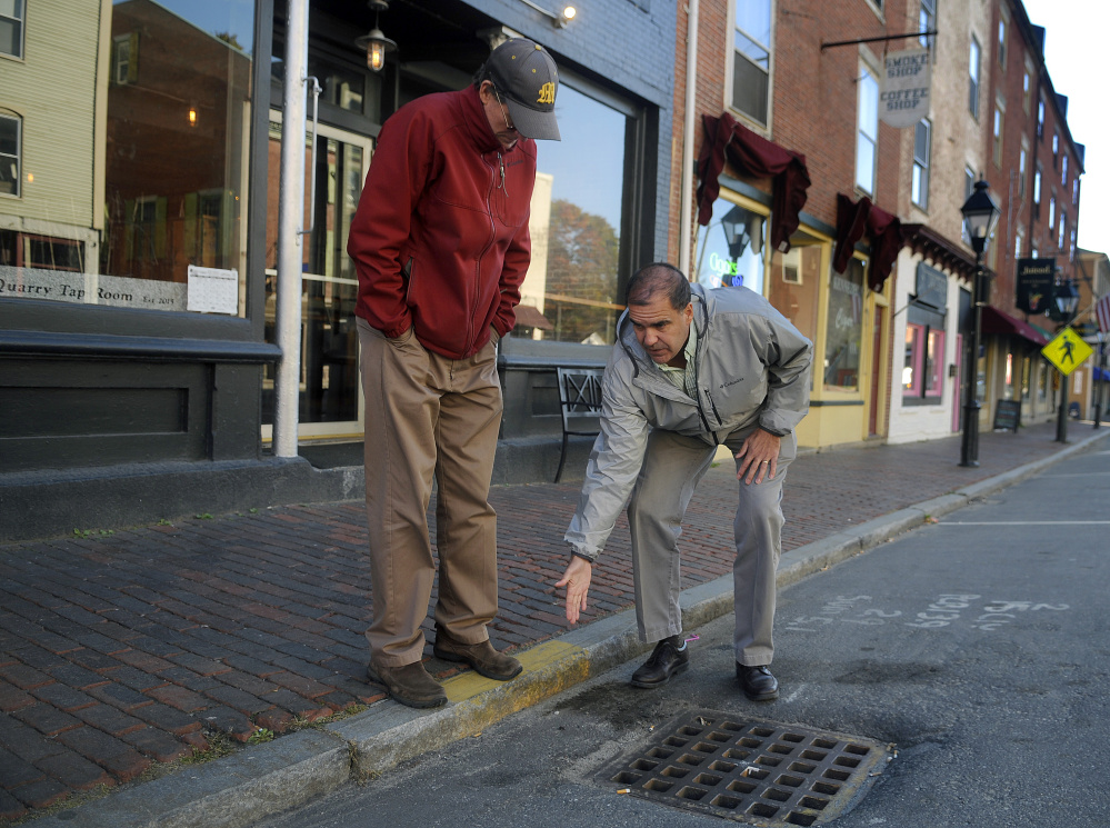 Maine Department of Transportation project engineer Ernie Martin, right, describes to Hallowell City Manager Stefan Pakulski how the agency plans to relocate storm drains on Water Street in Hallowell in this October file photo.