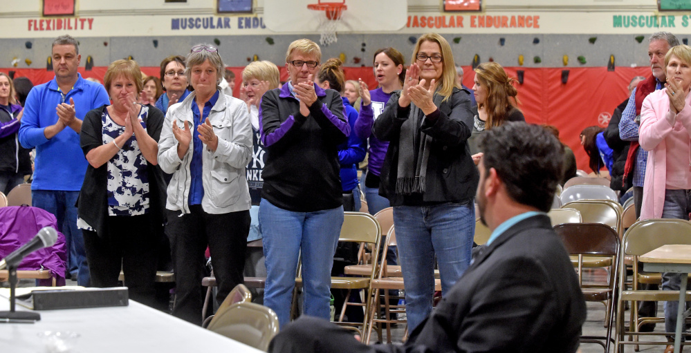Supporters, including faculty, parents and students, give Don Reiter, sitting at the table far right, a standing ovation during his dismissal hearing before the Waterville Board of Education two weeks ago. Reiter was fired by the board on the hearing's third night Monday.