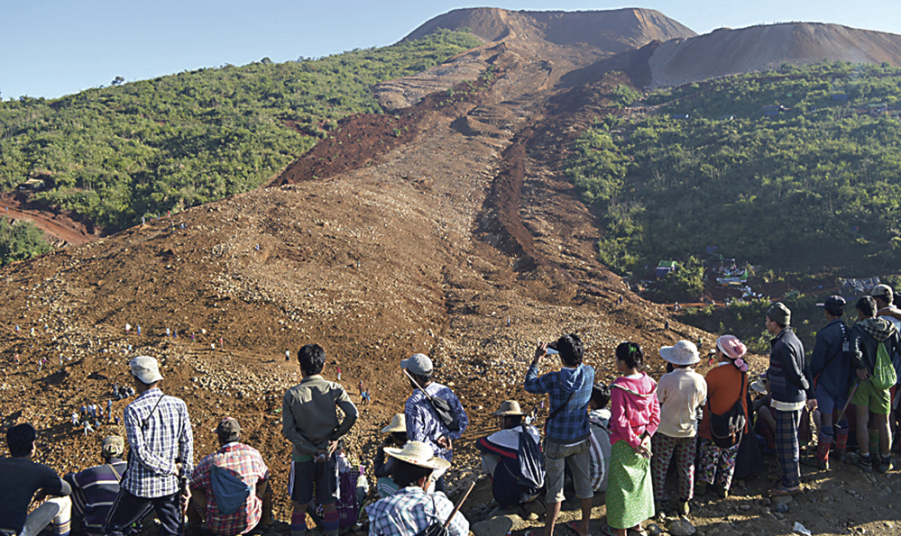 People look over an area covered by a landslide at Phakant jade mine in Kachin State, Myanmar, on Saturday. The landslide near the jade mine in northern Myanmar killed about 100 people and left many missing.
