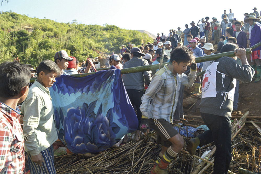 Myanmar Red Cross workers and people carry victims at a landslide affected area at Phakant jade mine, Kachin State, Myanmar.
