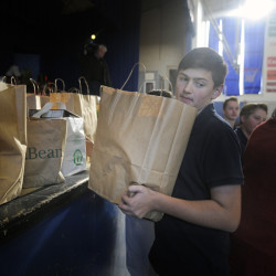 St. Michael School eight grader Drew Dionne carries a bag of Thanksgiving groceries Monday to people waiting in line at the Augusta Catholic school for food.