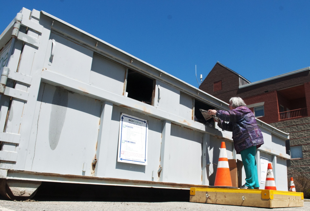 Laurie Southard tosses her recyclables into the container in May in the back lot of City Center in Augusta. City council may consider adding another recycling location on the city's west side.