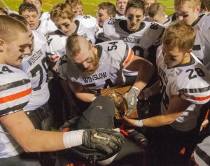 Members of the Winslow football team hold the Gold Ball for former coach Jim Poulin to kiss after they won the Class C championship Saturday at Fitzpatrick Stadium in Portland.