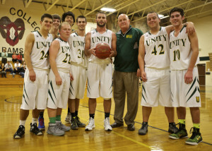 Members of the Unity College men's basketball team stand around senior guard Peter Kopacz after Kopacz scored his 1,000th career point in a game against the University of Maine at Machias on Nov. 10.