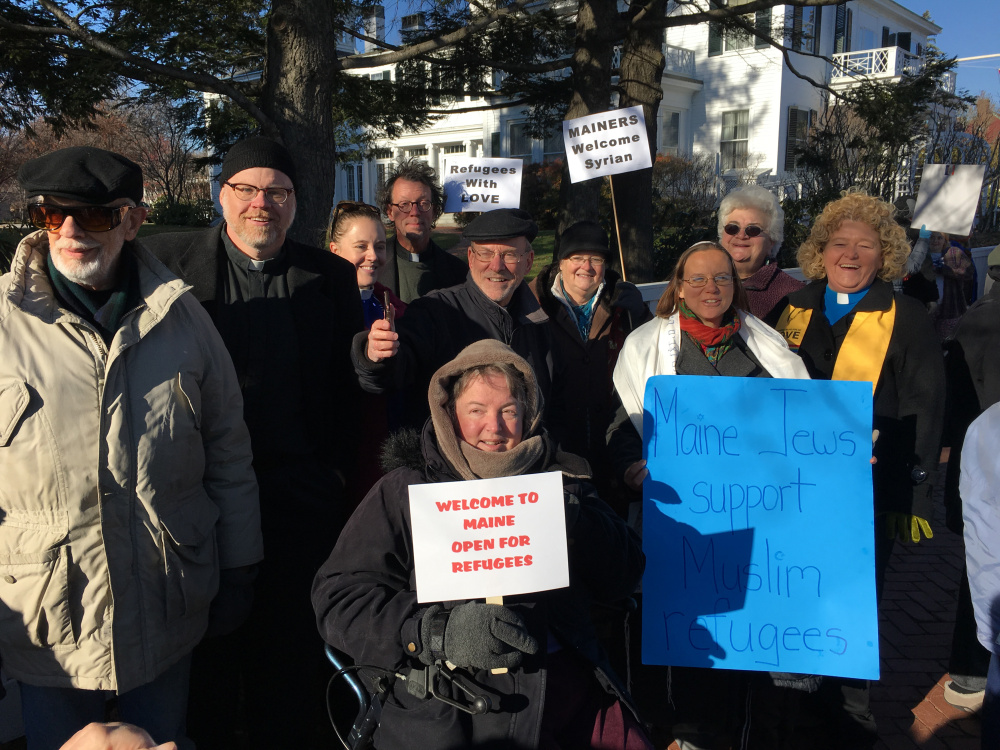 About 100 people held a vigil outside the Blaine House on Wednesday to show their support for Syrian refugees.