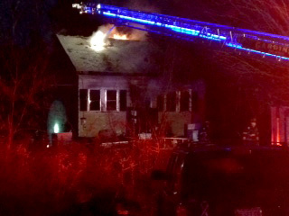 Flames shoot out the roof of a home on Old Brunswick Road in Gardiner Wednesday afternoon.