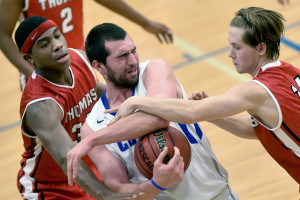 Thomas College's Dayne Savage, right, fouls Colby College's Chris Hudnut, middle, as Thomas' Carlos Gonzalez helps defend during a non-conference game Wednesday.