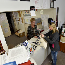 Kristina Cannon with Main Street Skowhegan delivers a bag of Small Business Passports to Doreen Poulin, owner of Key Appliance on Main Street in Skowhegan on Wednesday. Shoppers can use the passports at downtown and Madison stores Saturday, and the person with the most stamps wins a gift card.