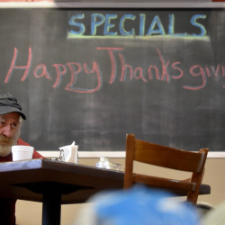 Colby Burdin takes a moment to enjoy a Thanksgiving dinner with all the fixings at the Cambridge General Store on Main Street in Cambridge on Thursday. This is the first year the store has hosted the dinner but hopes to make it an annual event. Donations were being accepted to buy Christmas gifts for local children.
