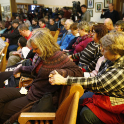 Women hold hands during a vigil in a church to mark Friday's shooting at a Planned Parenthood clinic Saturday in Colorado Springs, Colorado.