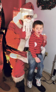 Between bites of a cookie, 3-year-old Sebastion Christie tells Santa Claus what he wants for Christmas at Santaville in Madison last year. A number of other Christmas events in the town were canceled last year because of rain, and organizers are hoping for better luck this year.