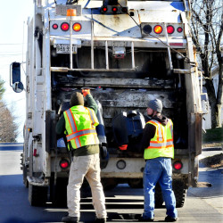 Winslow Public Works employees Josh Whitman, left, and Jacob Solomon fill a trash truck on Monday. A survey shows that Winslow residents support of more recycling in town, but are not in favor of a pay-per-bag garbage collection program.